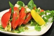 トマトとモッツァレラチーズのカプレーゼ¥650 完熟トマトにイタリア産のモッツァレラチーズとバジルを挟んだサラダ。