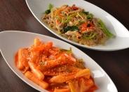 (手前)「トッポギ」うるち米で作られた棒状の餅とコチュジャンと砂糖で甘辛く炒めている本場韓国代表の味。(奥)「チャプチェ」春雨、牛肉と野菜たっぷり!低カロリーでヘルシー、ボリューム満点!